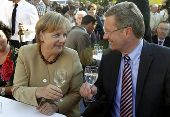 German Chancellor Merkel toasts with Lower Saxony federal state Prime Minister Wulff during summer reception in Berlin