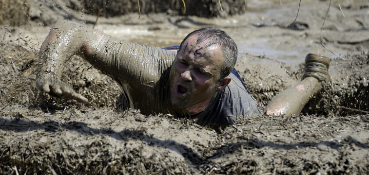 """A man crosses the finish line during the """"Tough Mudder"""" obstacle course event in San Bernardino, California"""