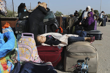 Palestinian girl hoping to cross into Egypt sleeps on suitcases as she waits with family at Rafah crossing between Egypt and southern Gaza Strip