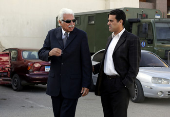 Former Egyptian Prime Minister Ahmed Nazif walks with his son outside of a court after his trial was delayed, in the outskirts of Cairo