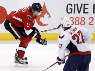 Ottawa Senators' Michalek holds the puck in front of Washington Capitals' Alzner during their NHL hockey game in Ottawa