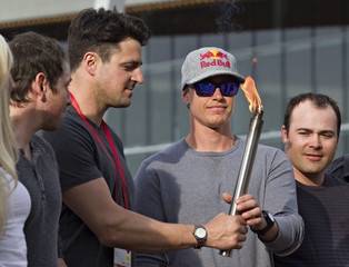 Canadian luger Samuel Edney hands downhill skier Erik Guay a torch during a ceremony in Vancouver