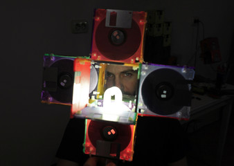 Romanian actor Alin Teglas is seen through a lamp made from recycled floppy disks in his kitchen-workshop in Bucharest