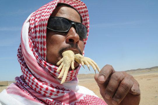 A man eats a part of an Uromastyx lizard, also known as a dabb lizard, in a desert near Tabuk