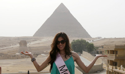 A contestant of Miss ECO Universe poses for a pictures with pyramids behind, on the outskirts of Cairo