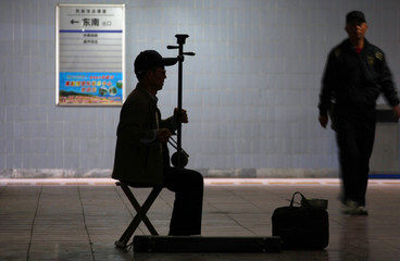 "Pedestrian walks past man playing two-stringed bowed musical instrument called ""erhu"", also known as Chinese violin, in underground walkway in central Beijing"