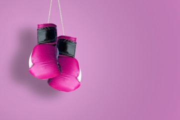 Pink hanging boxing gloves hanging against a pink background. Empty copy space for Editor's text.