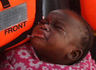A migrant infant cries after she was rescued from an overcrowded raft, as lifeguards from the Spanish NGO Proactiva Open Arms rescue all 112 on aboard