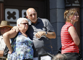 People look at the devastation caused by derailment following a visit to Sainte-Agnes Church in Lac-Megantic