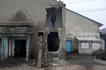 A migrant stands outside a derelict customs warehouse in Belgrade