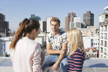 Friends meeting on a rooftop terrace in summer