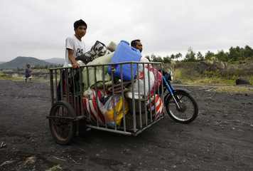 Evacuees with their belongings head home after departing the evacuation center at Gogon elementary school in Legazpi city