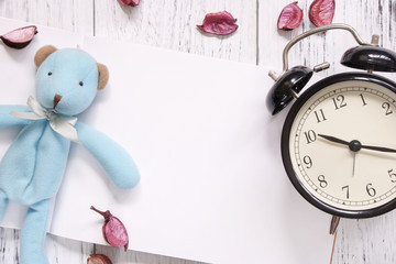 Stock Photography flat lay vintage white painted wood table blank note book petals blue bear alarm clock