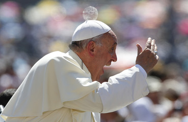 Pope Francis waves as he arrives to lead the weekly audience in Saint Peter's Square at the Vatican