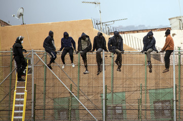 African migrants sit on top of a border fence as a Spanish Civil Guard officer stands on a ladder during an attempt to cross into Spanish territories, between Morocco and Spain's north African enclave of Melilla