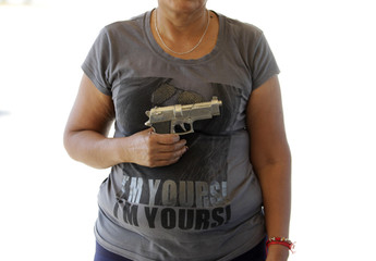 "A 42-year old woman holds a 22 mm calibre pistol before turning it in during the ""Voluntary Disarmament Programme"" in San Nicolas in Monterrey"