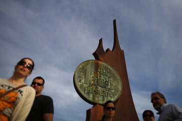 People walk past the monument of a huge replica of a Spanish peseta coin, the former Spanish currency used before the euro, in Fuengirola