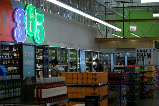 Employees arrange beer and wine at a 365 by Whole Foods Market grocery store is pictured ahead of its opening day in Los Angeles
