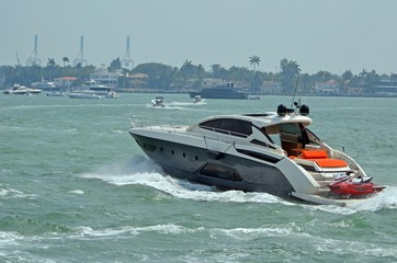 Luxurious cabin cruiser making its way through choppy water on the florida intra-coastal waterway off Miami Beach.