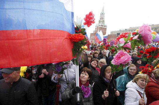 People walk with flags and artificial flowers at Red Square during a May Day rally in Moscow