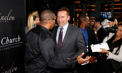 """Cast member Murphy greets former California Governor Schwarzenegger at the premiere of """"Mr. Church"""" in Los Angeles"""