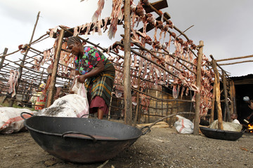 "A fish trader dries fish skeletons on wooden poles outside her stall at the Obunga ""mgongo-wazi"" fish frying market in Kisumu"