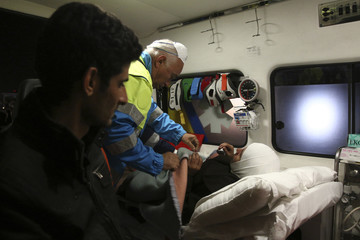 A migrant is helped by ambulance staff in the Sicilian harbour of Augusta