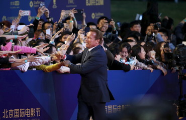 U.S. actor Arnold Schwarzenegger shakes hands with fans during the red carpet ceremony of the Beijing International Film Festival, in Beijing