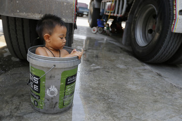 A boy bathes in a bucket next to his father's rice truck outside a rice mill in the central province of Chainat