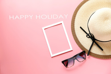 Happy Holiday text and Panama hats and sunglasses on pink background ,copy space