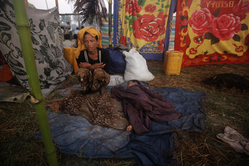 A woman displaced by the recent violence in Pauktaw sits by her sleeping child at Owntaw refugee camp for Muslims outside Sittwe