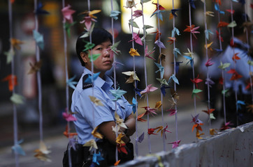 A police officer stands behind origami paper cranes at a protest site after some barricades were removed, in Causeway Bay