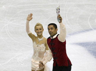 Savchenko and Szolkowy of Germany wave after performing during the pairs free programme at the ISU Grand Prix of Figure Skating Final in Fukuoka