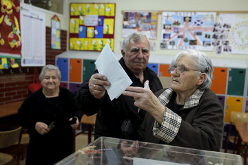 People cast their votes at a polling station during elections in Belgrade