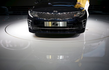 A model poses next to a Kia Motor's new K5 as at the Seoul Motor Show 2015 in Goyang