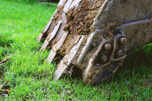 a part of backhoe digging mud, green grass background