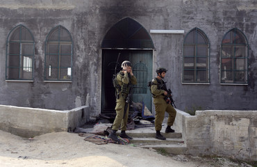 Israeli soldiers stand near the damaged door of a mosque near Nablus