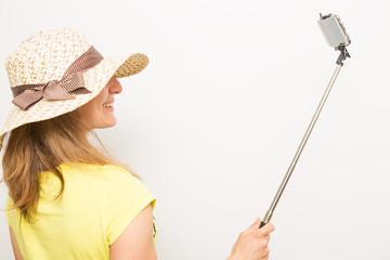 ragazza scatta un selfie con il bastone e lo smartphone