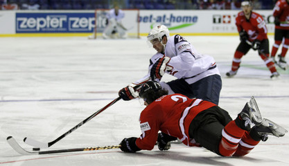 Gerber of Switzerland challenges Stapleton of the U.S. during their qualification round Group F game at the Ice Hockey World Championships in Kosice