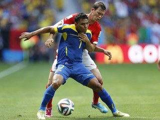 Ecuador's Montero and Switzerland's Lichtsteiner  fight for the ball during their 2014 World Cup Group E soccer match at the Brasilia national stadium in Brasilia