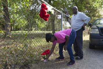 Denise Singleton (L) of North Charleston and Nick Jenkins of Ladson, South Carolina, place flowers at a small memorial near where Walter Scott was shot in North Charleston