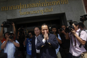 Embattled FIFA executive committee member Worawi Makudi greets supporters gathered while he addresses reporters in Bangkok