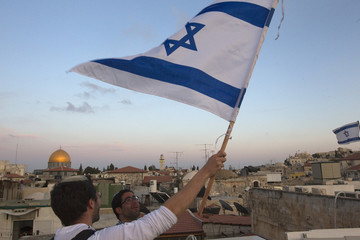 An Israeli holds up a national flag atop a building in Jerusalem's Old City