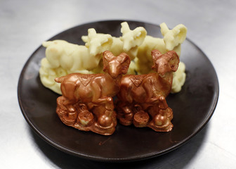 Goat-shaped chocolates displayed on a plate while a chef prepares to make a cake celebrating the upcoming Chinese Lunar New Year, during a photo opportunity at a kitchen of Kerry Hotel in Beijing