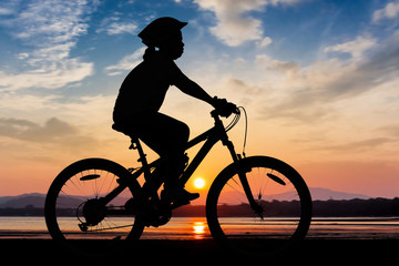 Girl cycling at the beach twilight time