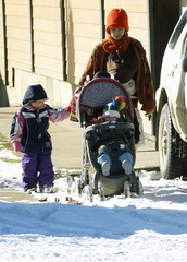 A family struggles to push a stroller through fresh snow in Nederland
