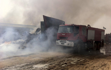 A firefighter truck is seen near smoke and rubble of buildings damaged after explosions that took place at midnight, in the Salaheddin district of Tripoli