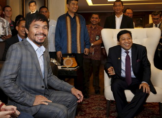 Filipino boxing superstar Manny Pacquiao smiles while meeting  with the head of Indonesia's House of Representatives (DPR) Setya Novanto during a courtesy call in Jakarta, Indonesia