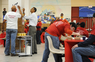 Obama paints a cartoon on the walls at Stuart-Hobson Middle School on Capitol Hill in Washington