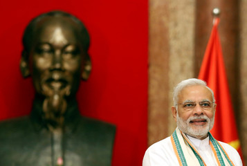 India's PM Modi is seen in front of a statue of late Vietnamese revolutionary leader Ho Chi Minh at the Presidential Palace in Hanoi, Vietnam